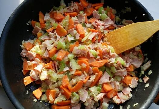 Овощи и грудинка на сковороде для тосканского супа с полбой