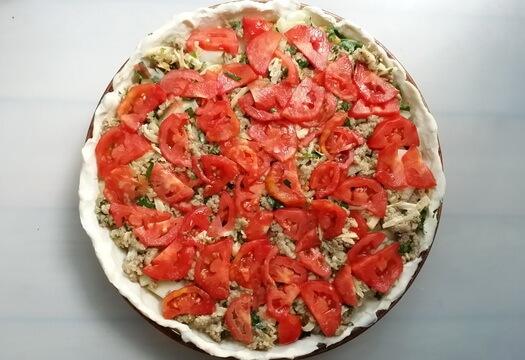 Выложите тонко нарезанные помидоры поверх начинки